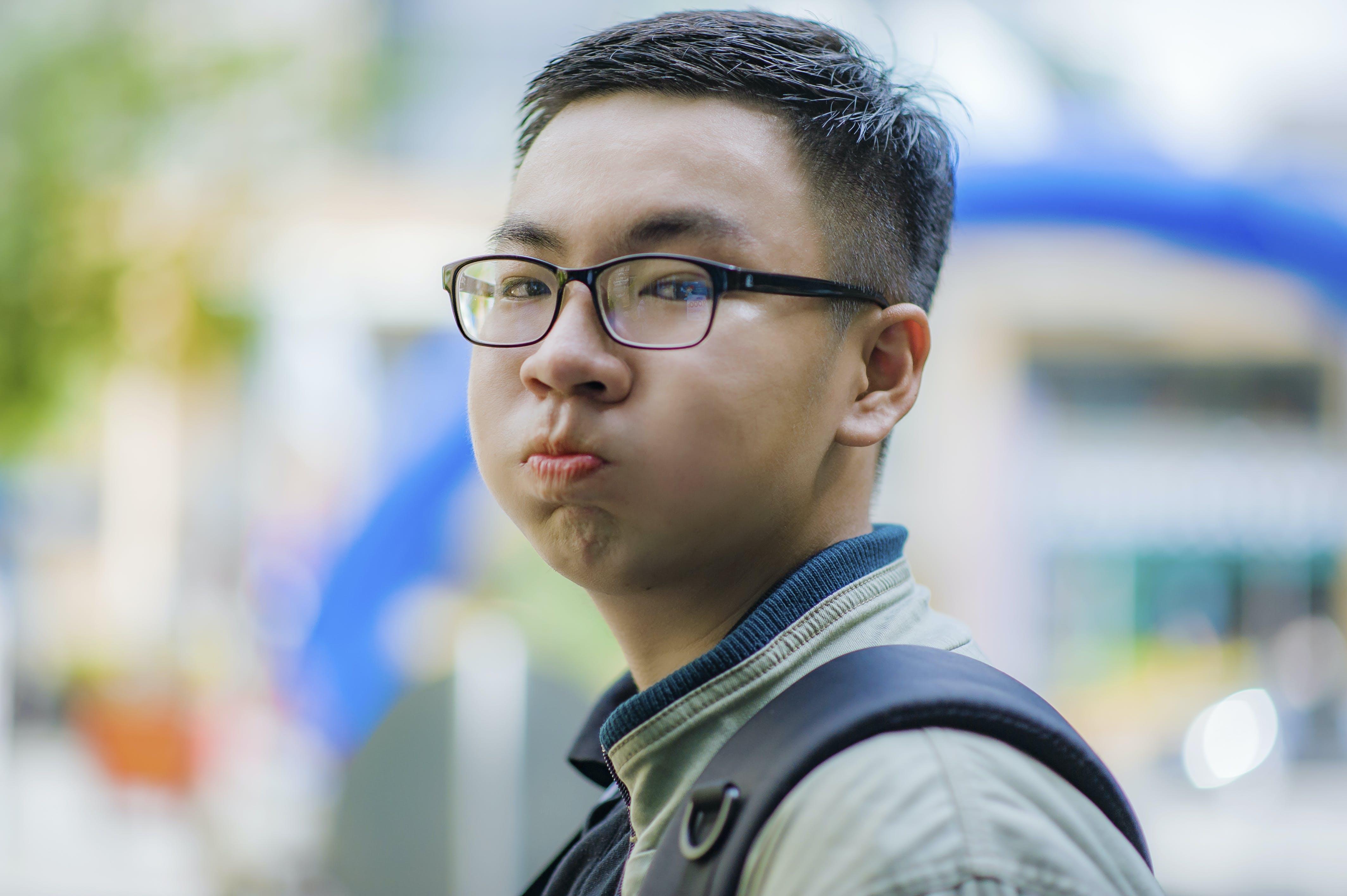 Man Wearing Gray Jacket and Black Framed Eyeglasses