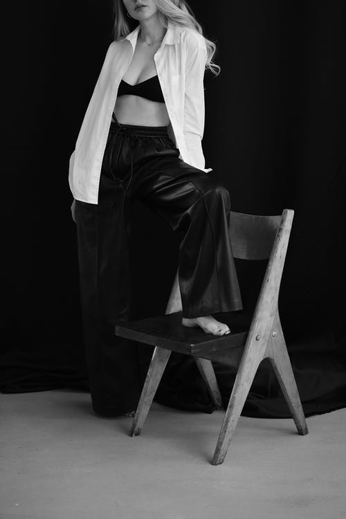 Grayscale Photo of Woman in White Long Sleeve Shirt and Black Skirt Sitting on Chair