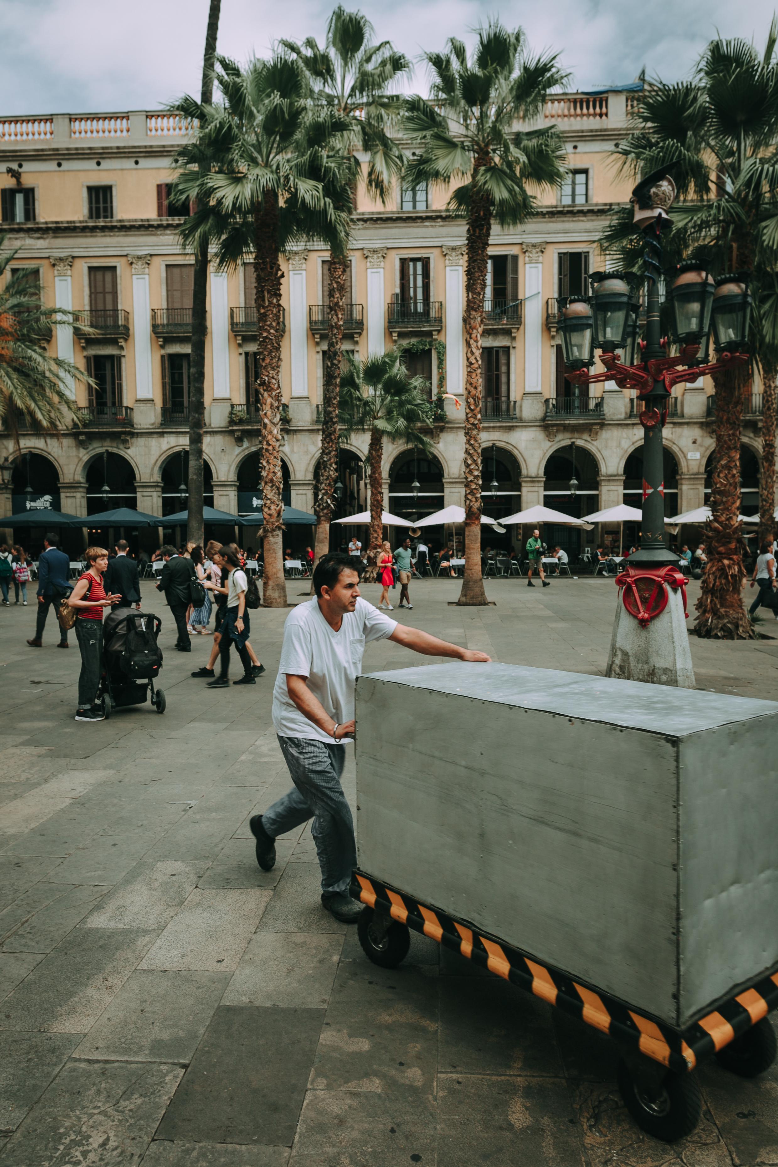 Man Pushing Gray Cart