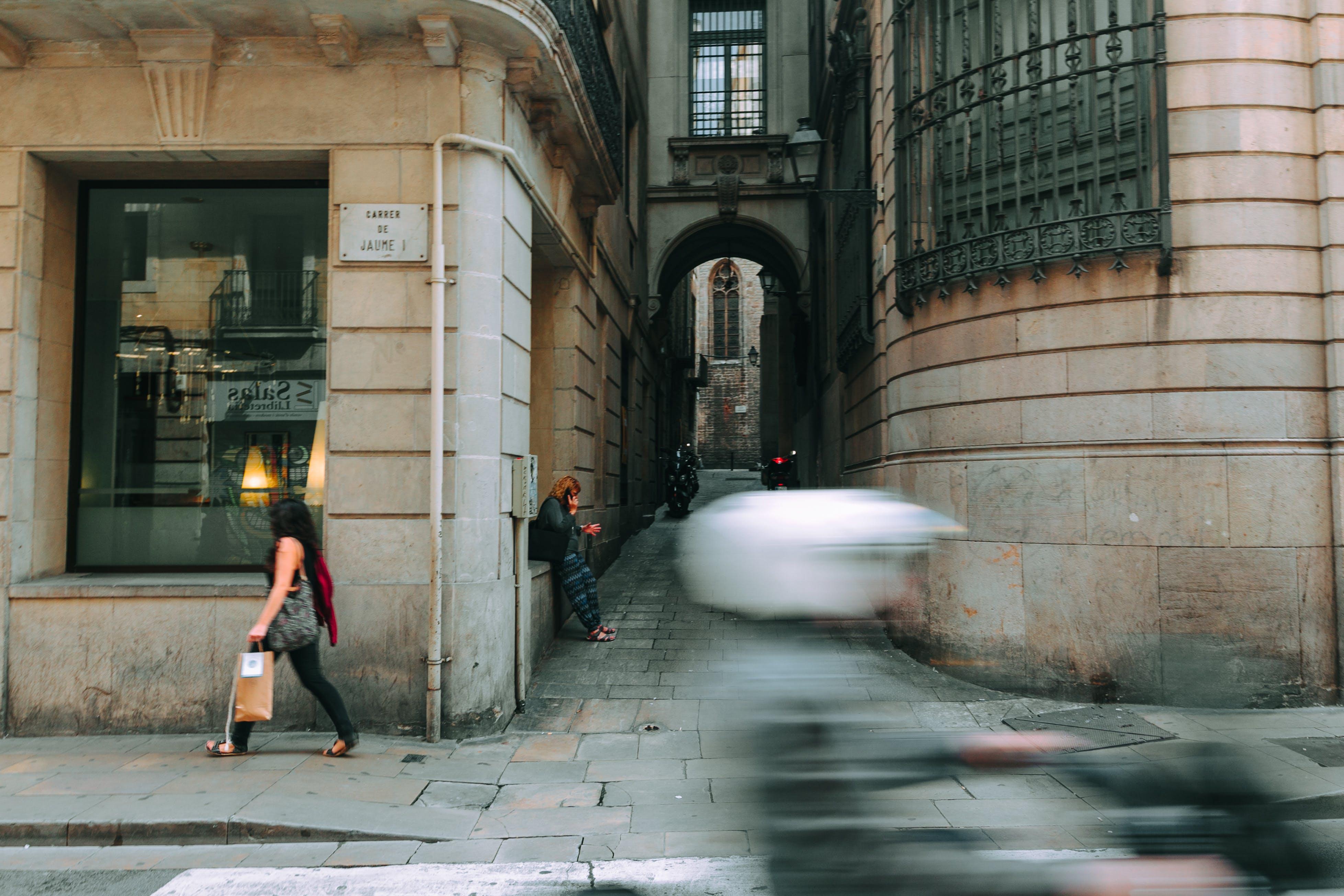 Woman in Black Walking Near Glass Window