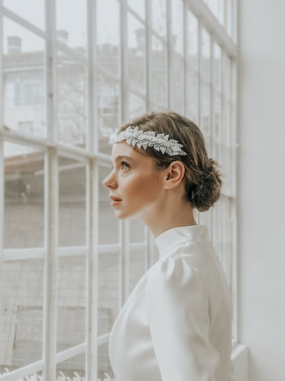 Side view of thoughtful young lady in white elegant outfit and barrette in room near windows in daytime