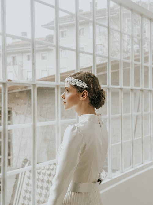Pensive young female in white elegant dress and hairband standing near windows in room in daylight