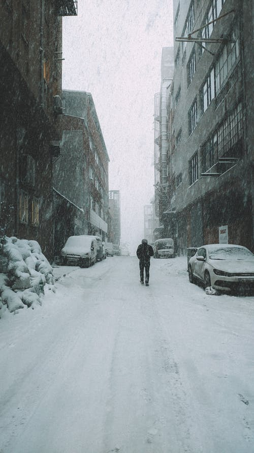 Person Walking on Snow Covered Road