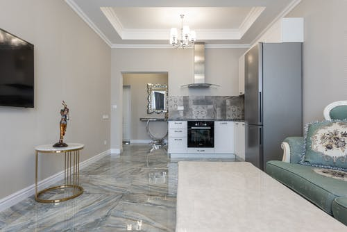 Contemporary kitchen and living room interior with sofa against tables and electric appliances under ceiling with chandelier in house