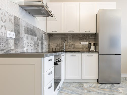 Modern kitchen interior with white cabinets and fridge against electric kettle and ornamental wall in light house