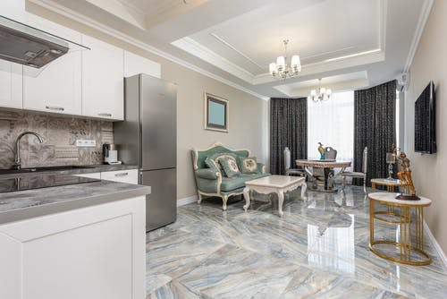 Classic living room and modern kitchen interior with tables against couch and refrigerator on marble floor at home
