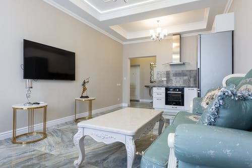Living room and kitchen interior with classic sofa against TV and electric appliances on marble floor at home