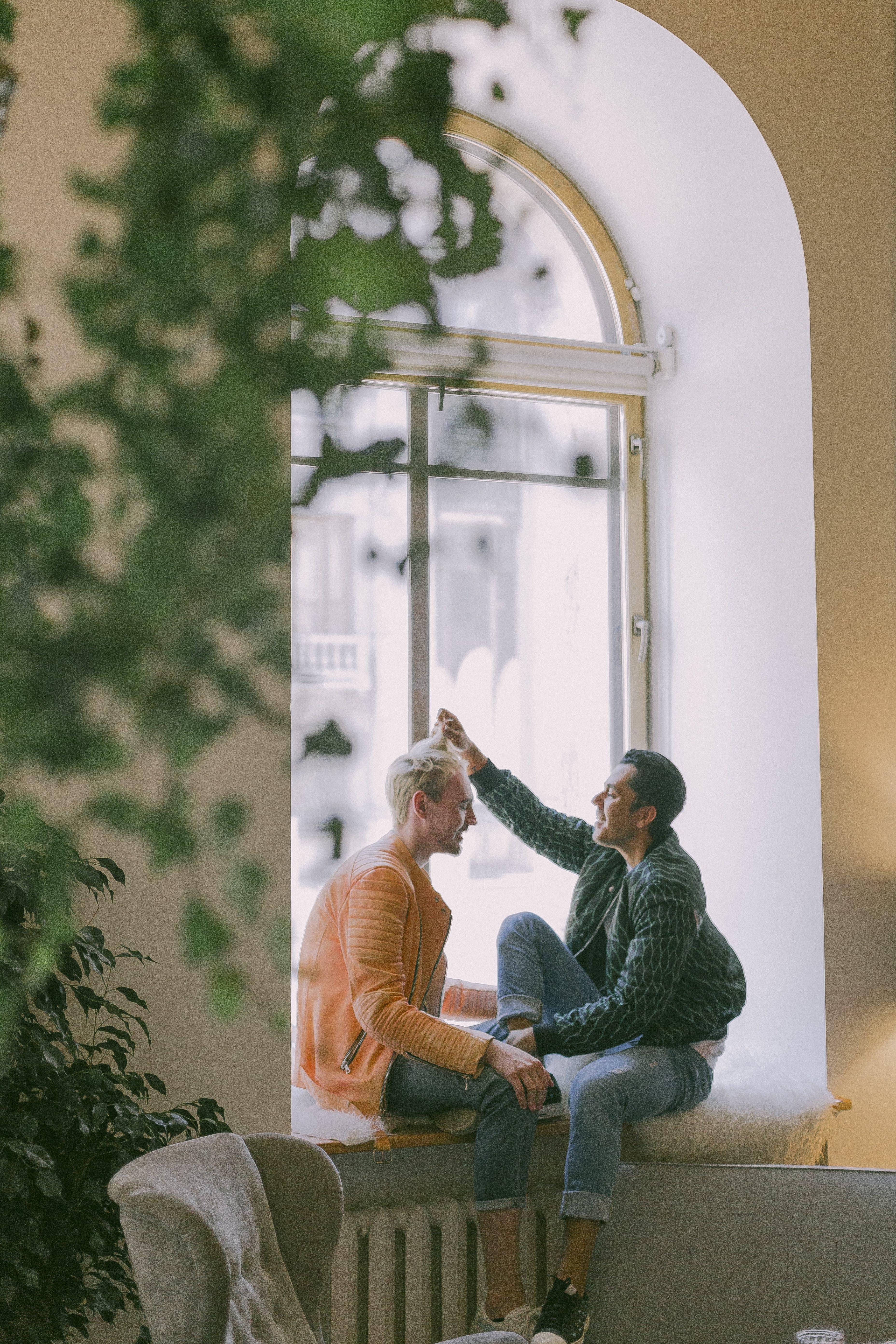 Man Wearing Green Jacket in Front of Man Wearing Orange Zip-up Jacket Sitting on Near the Window Photo