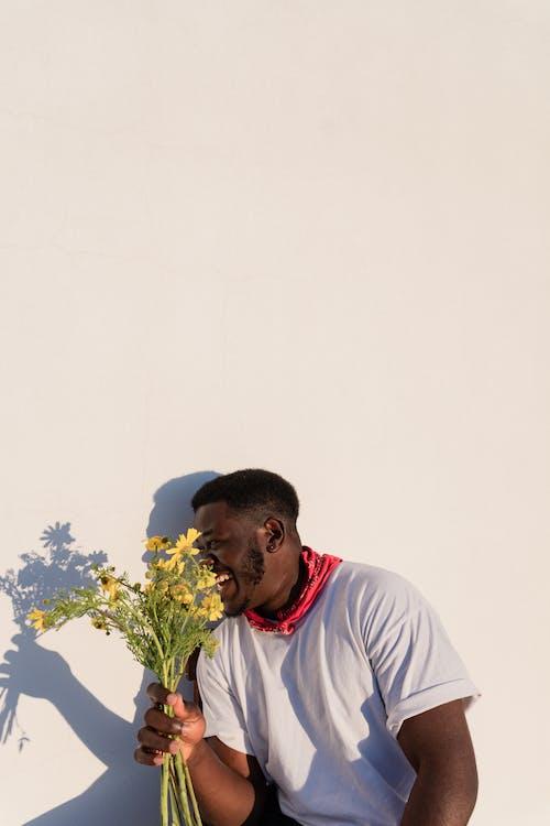 Man in White Crew Neck T-shirt Holding White Flower Bouquet