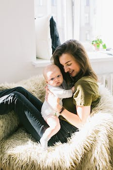 Woman Holding Baby While Sitting On Fur Bean Bag 183 Free