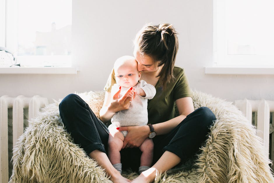 Woman Holding Baby While Sitting on Fur Bean Bag