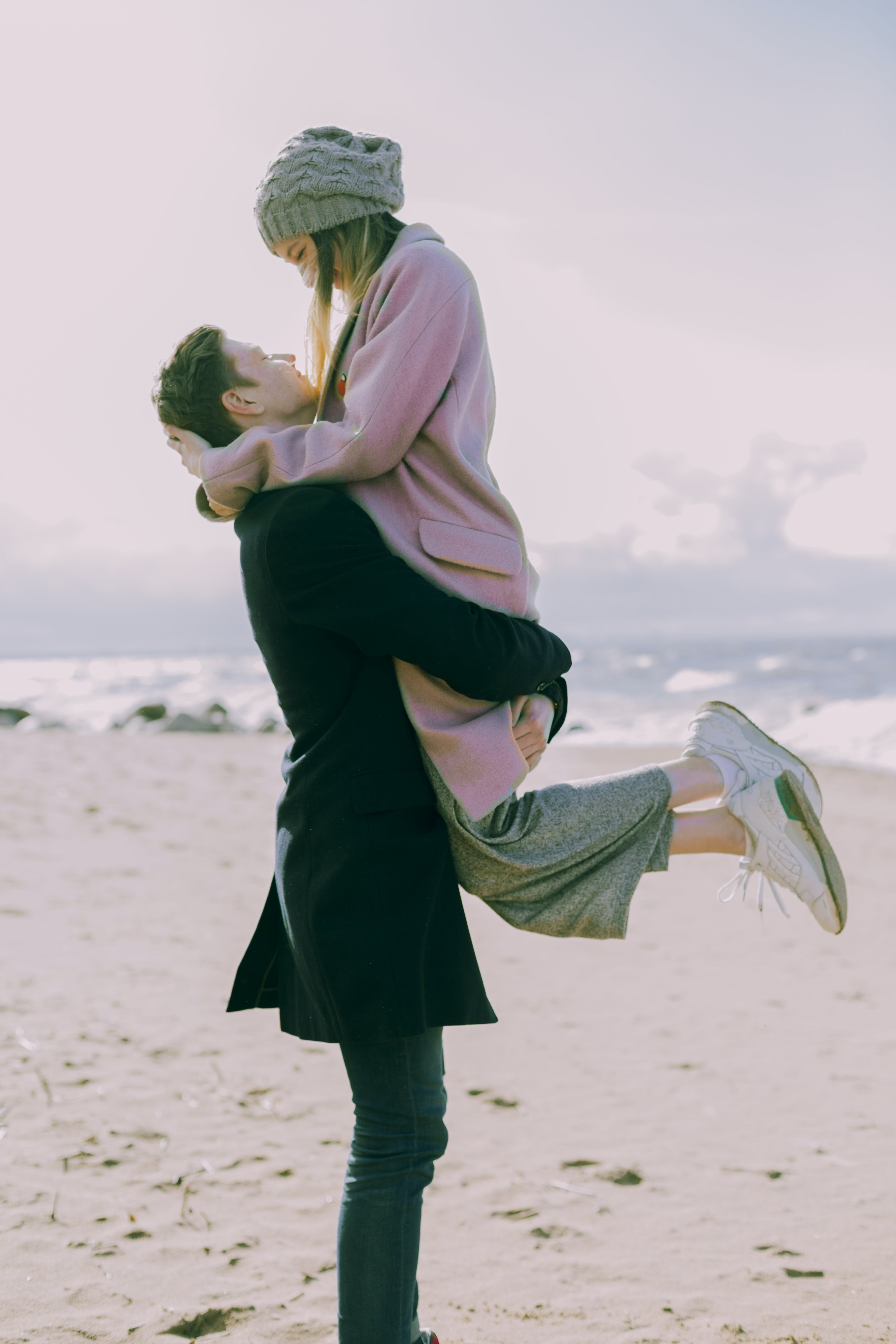 Man in Gray Coat Carrying Woman Wearing Pink Coat in Beach Near Shoreline and Body of Water