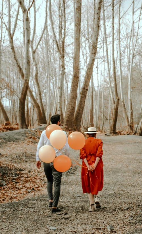 Back view full body of unrecognizable female wearing colorful dress and hat with balloons and man spending time together in park on birthday in autumn