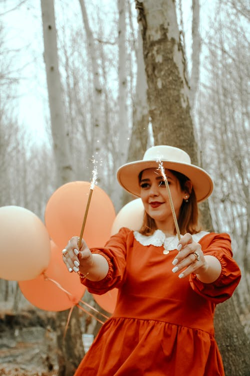 Cheerful female party entertainer wearing festive costume standing with sparklers against balloons and celebrating in park in autumn in daylight