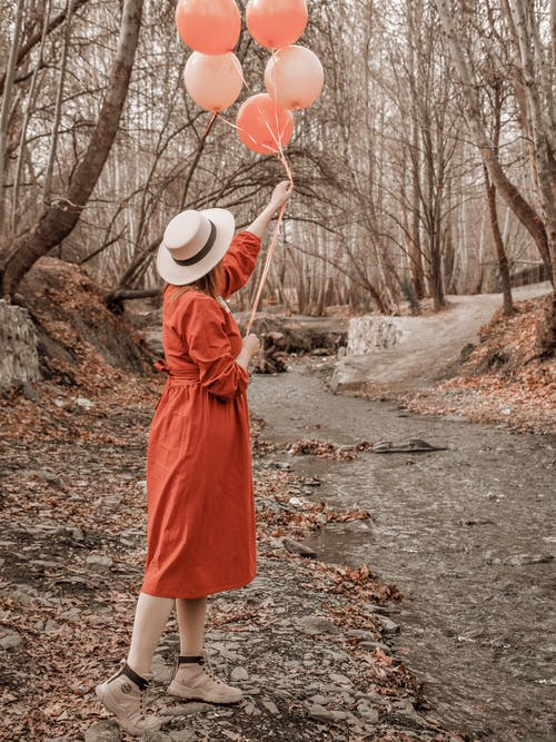 Woman in a Red Dress Holding Five Balloons