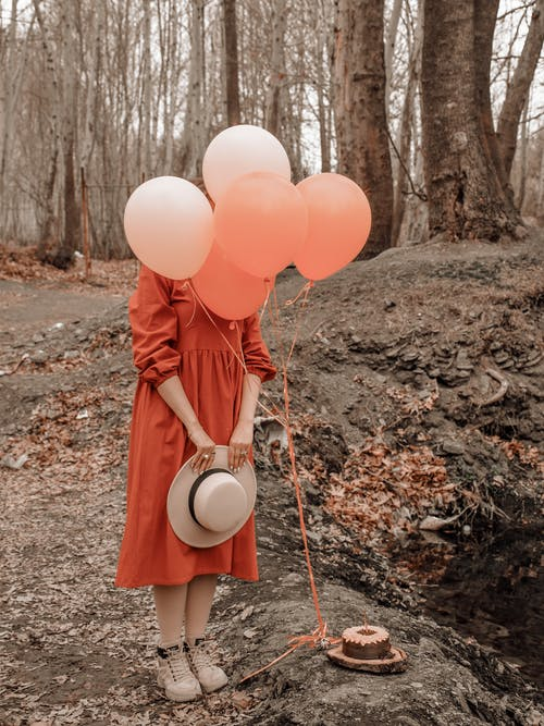 Full body of anonymous female model wearing dress with hat in hands standing behind colorful balloons and cake in woods in daytime
