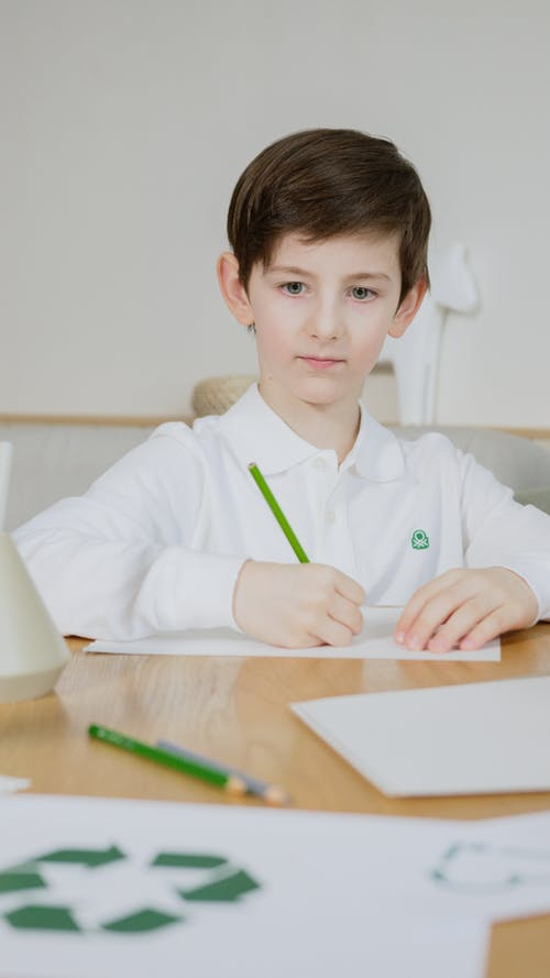 A Boy Looking On A Paper Across The Table