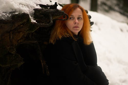 Emotionless adult female in black coat near fallen tree trunk with roots in snowy woods in winter day while looking away pensively