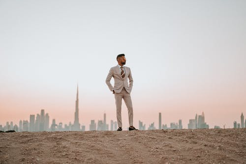 Man in White Suit Standing on Brown Sand
