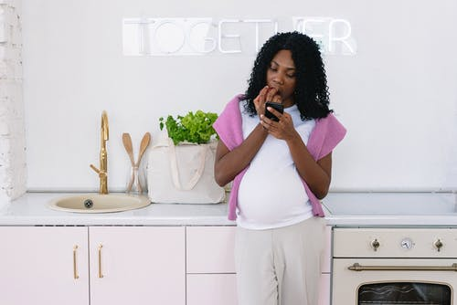 Black pregnant woman with smartphone eating in kitchen