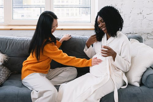 Cheerful Asian lesbian touching tummy of happy pregnant African American female while sitting on couch in living room at home