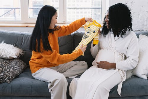 Side view of cheerful Asian female showing baby clothing to happy pregnant African American woman while sitting on couch at home