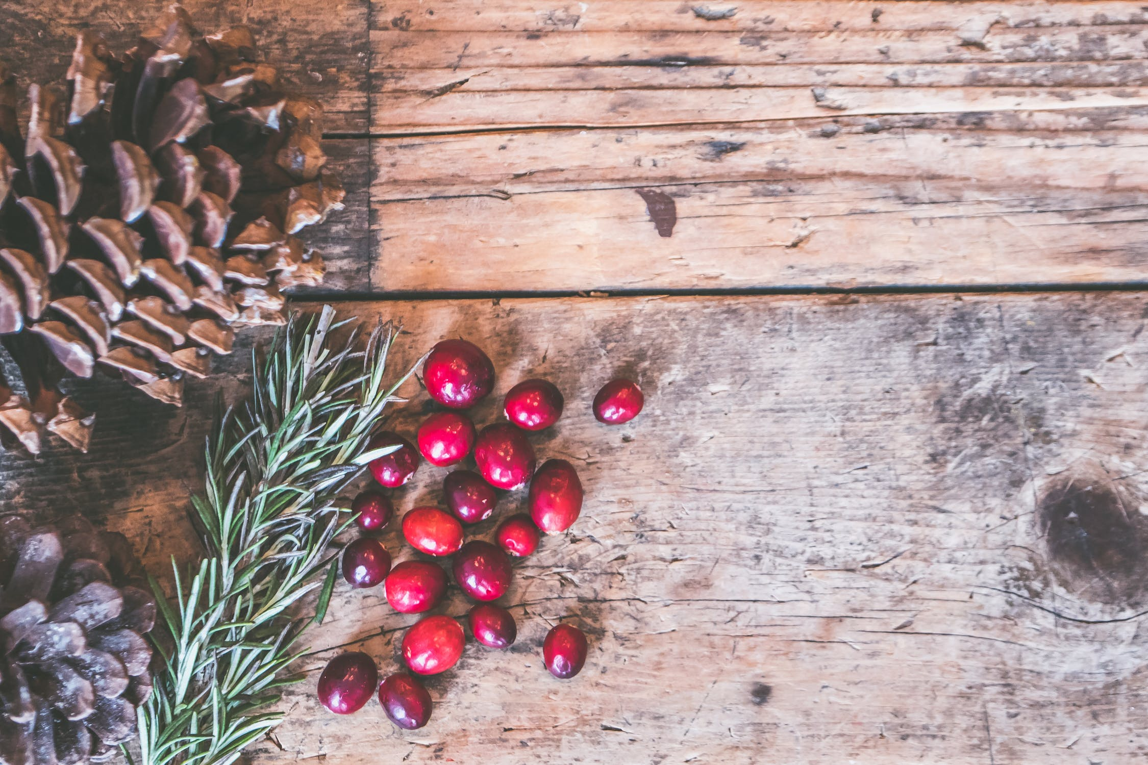 A birdseye view of a wooden table with holly, pomegranate seeds, and a pinecone sitting on it. Photo by pexels user Jessica Lewis. Photo used courtesy of pexels.com.
