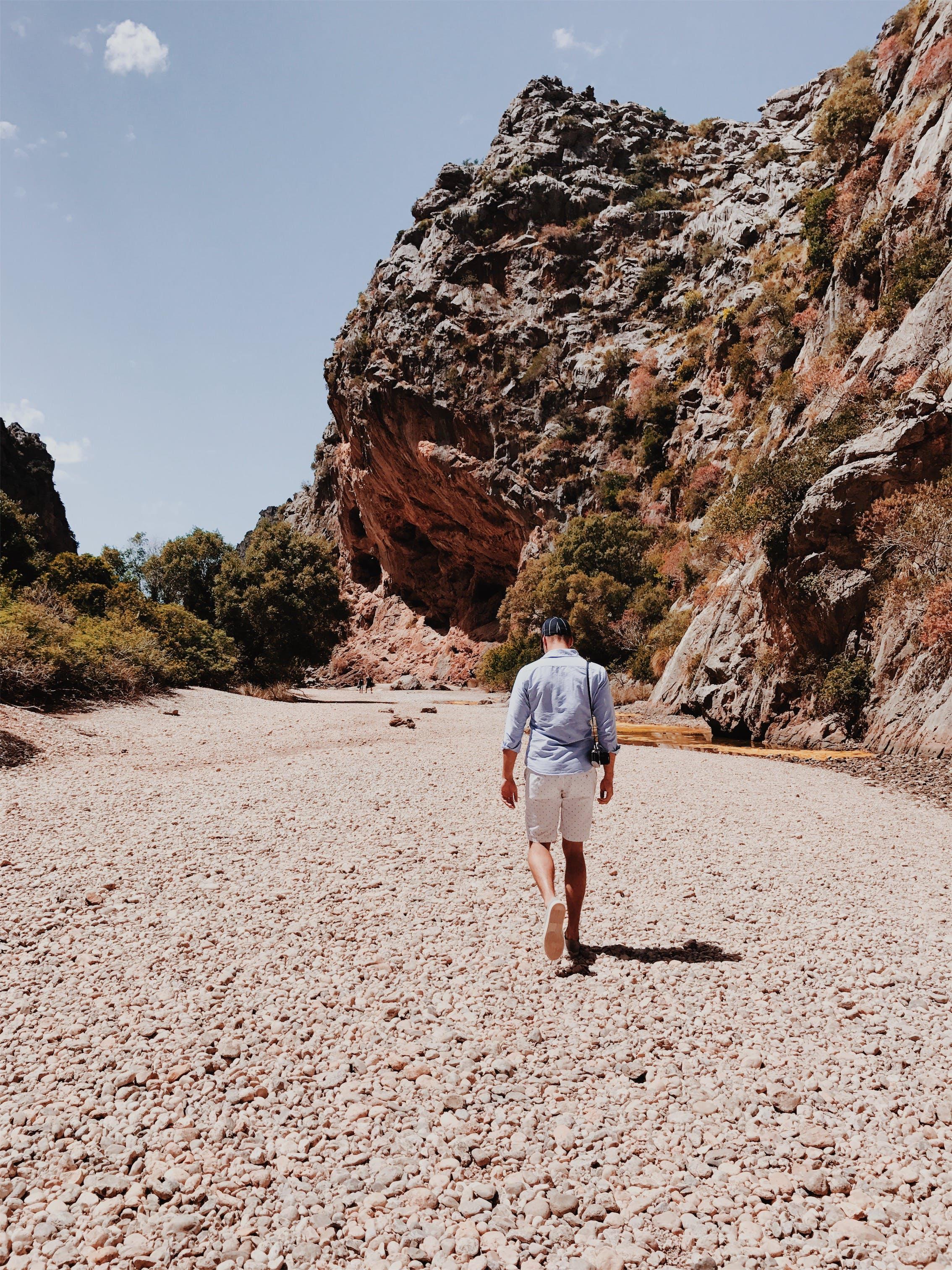 Person Walking Near Rock Formation