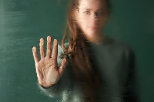Woman's Palm on Wet Glass Wall