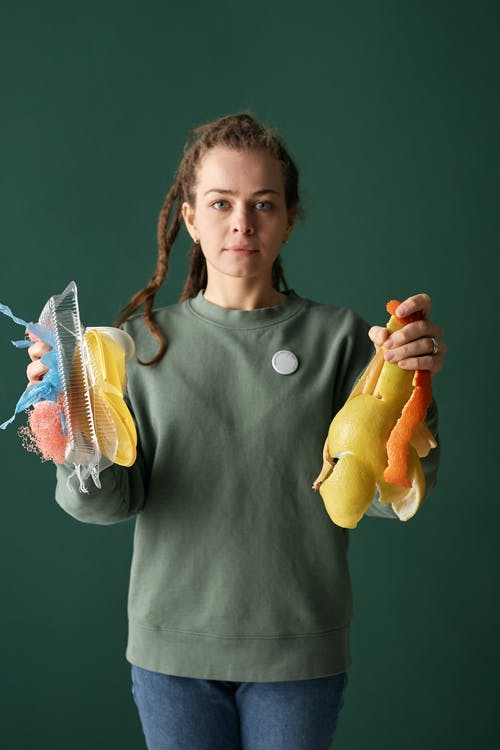 Woman Holding Plastic and Organic Trash in Hands