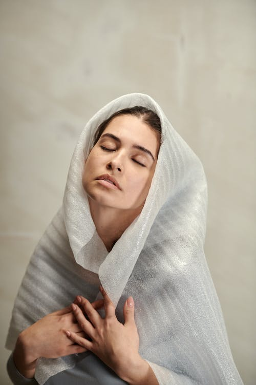 Woman in White Hijab Covering Her Body With White Blanket