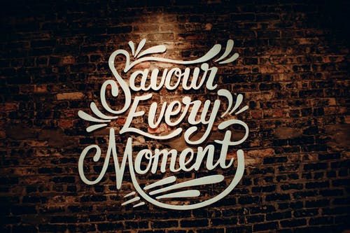 White creative signboard with Savour Every Moment inscription with decorative elements hanging on shabby brown brick wall of contemporary cafeteria