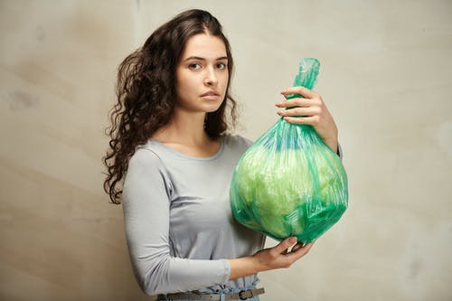 Woman in Teal Long Sleeve Shirt Holding Green Plastic Bag