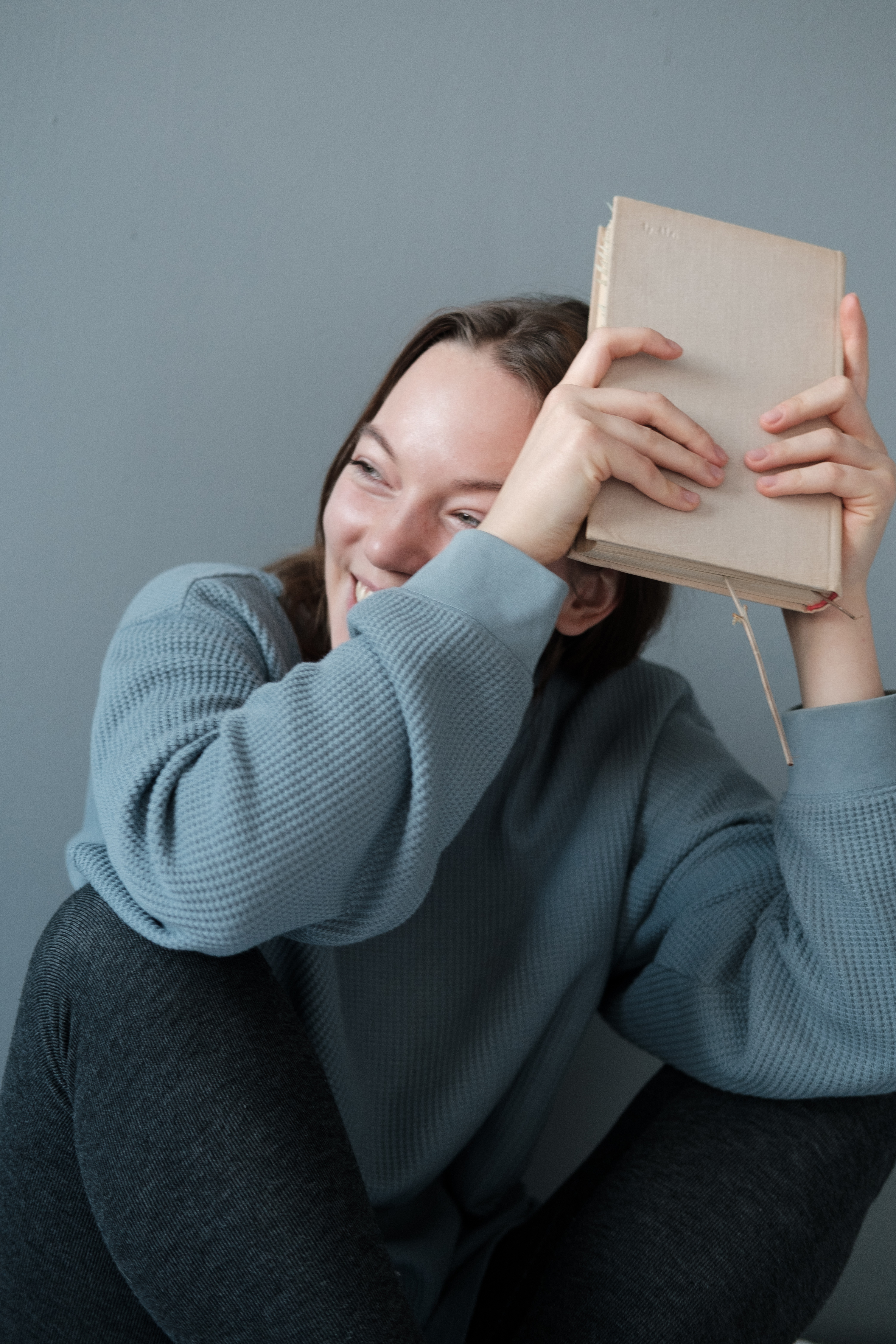 smiling woman in gray warm clothes sitting with book