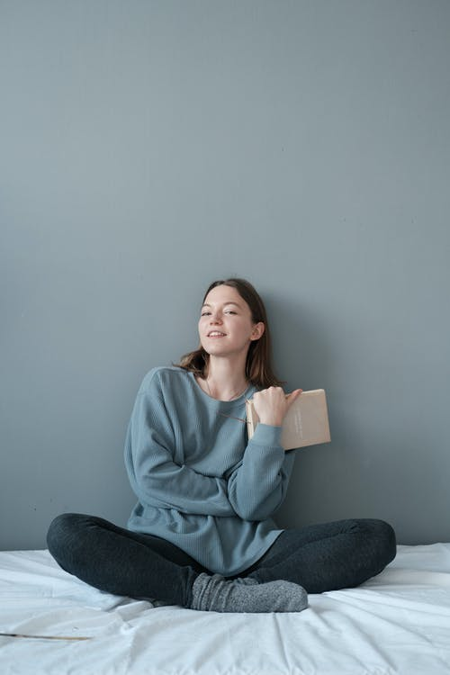 Young content female with textbook sitting with crossed legs on crumpled bed sheet while looking at camera on gray background