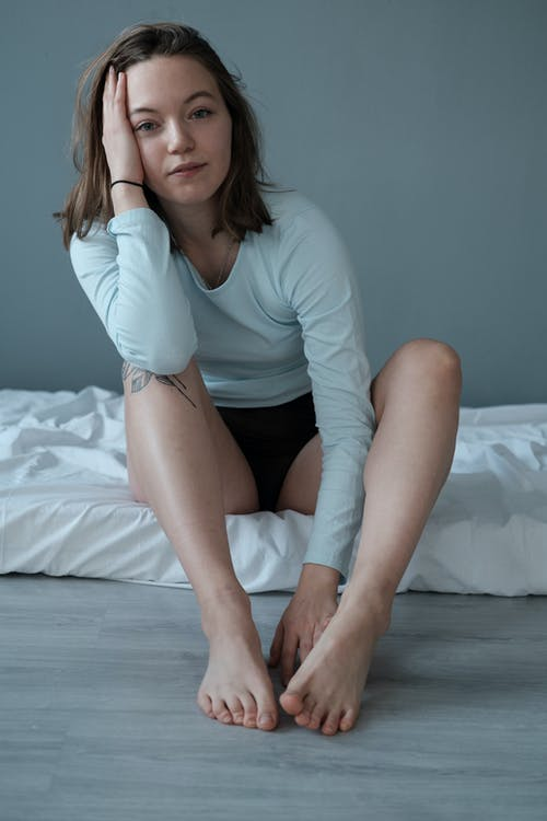 Full body of peaceful barefooted female in sleepwear sitting on mattress while keeping hand on head and looking at camera