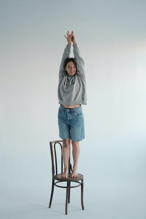 Full body of glad young female wearing casual hoodie and denim shorts looking at camera while standing on wooden chair with raised arms