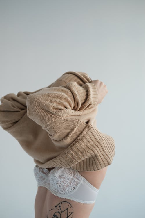 Woman in underwear putting on sweater