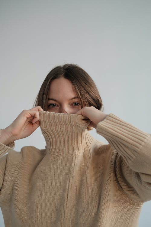 Young shy female hiding face behind warm sweater against gray background and looking at camera