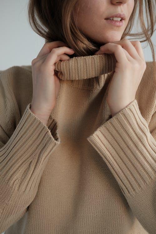 Crop gentle female with long hair wearing warm beige sweater in white studio