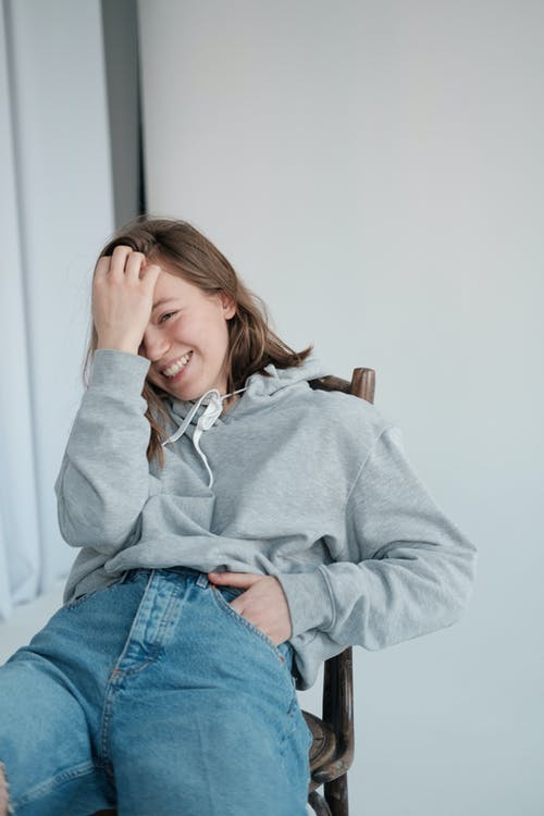 Positive young woman touching hair while laughing happily sitting on chair in studio and looking at camera