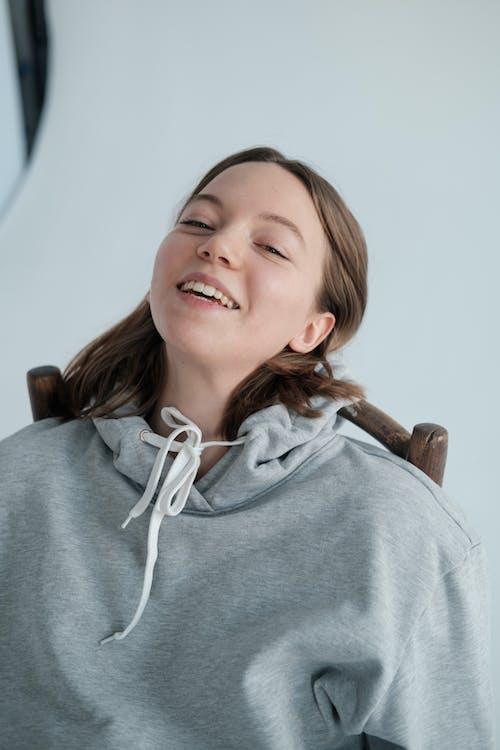 Smiling woman in hoodie sitting on chair in studio