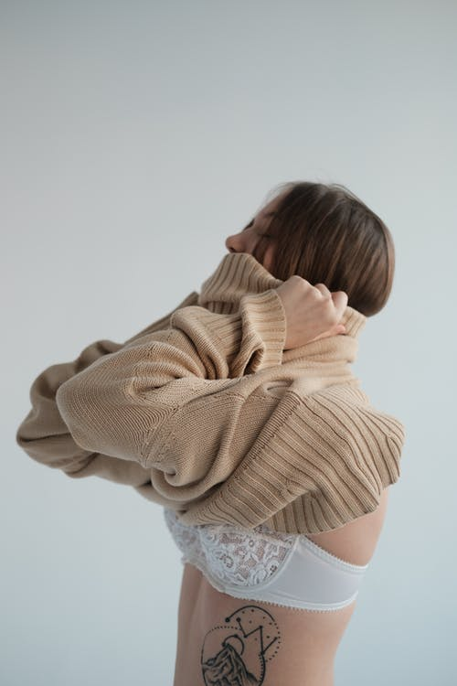 Side view of young female wearing underwear putting on soft beige sweater against gray background