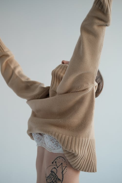 Woman putting on sweater over underwear