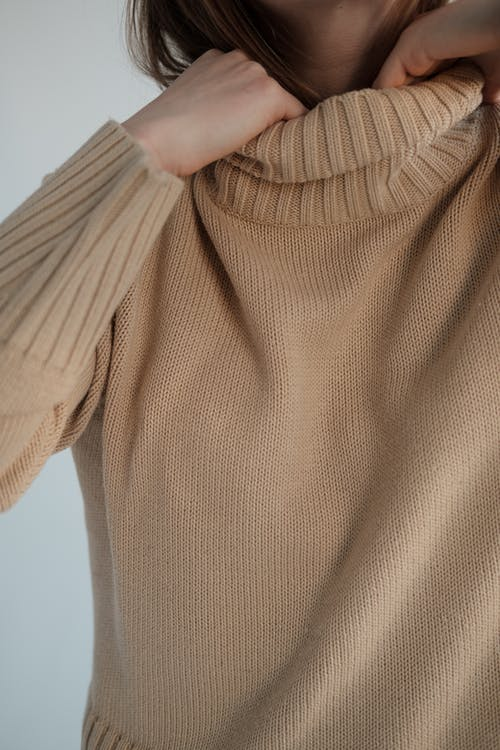 Crop unrecognizable female touching collar of warm sweater against gray background in studio