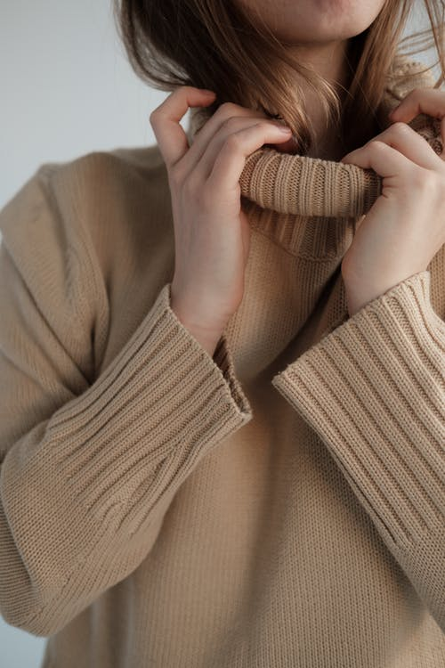 Crop unrecognizable female with long hair wearing soft warm sweater with long collar
