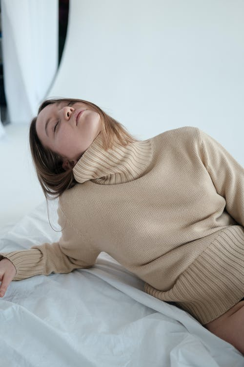 High angle of sleepy young female with closed eyes wearing turtleneck leaning on hand while lying on floor