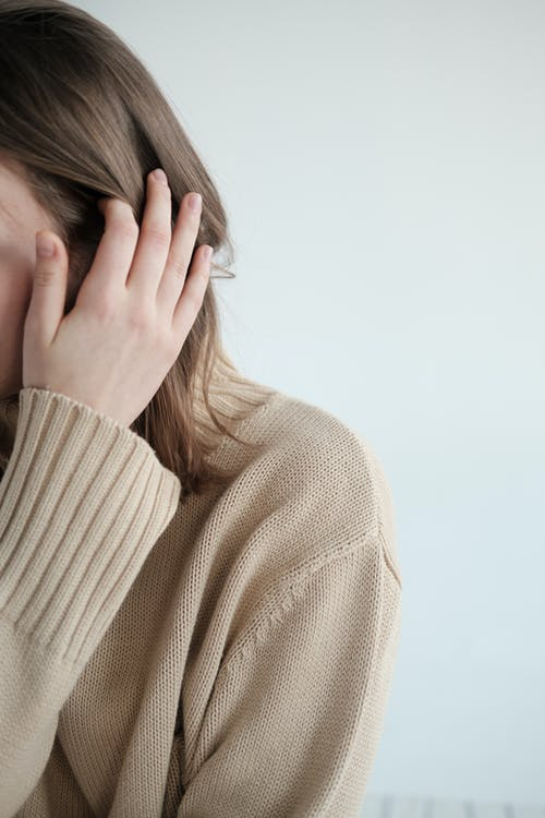 Young woman in sweater touching hair