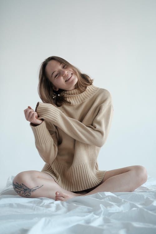 Full body of positive female wearing beige turtleneck sitting on bedsheet and smiling widely against white background
