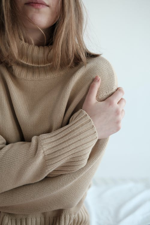 Crop unrecognizable female in warm sweater hugging herself gently while sitting on white bed